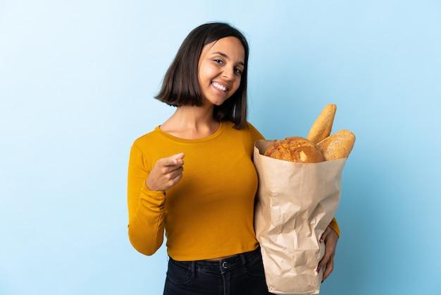 Giovane donna latina che compra alcuni pani isolati sulla parte anteriore indicante blu con l'espressione felice