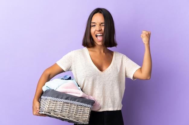Giovane donna latina che giudica un canestro di vestiti isolato sulla porpora che fa forte gesto