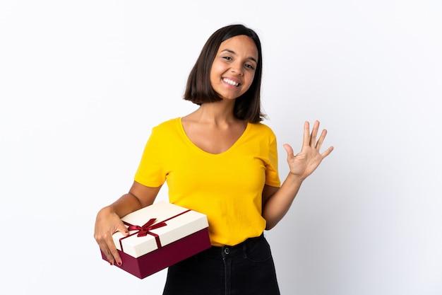 Giovane donna latina che giudica un regalo isolato su bianco che conta cinque con le dita