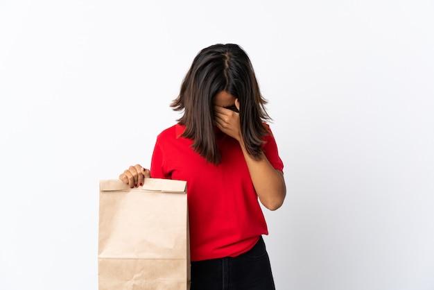 Giovane donna latina che giudica un sacchetto della spesa della drogheria isolato su bianco con l'espressione stanca e malata