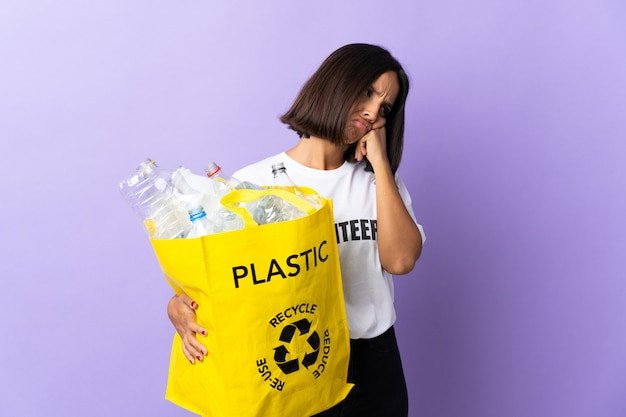 Giovane donna latina che giudica una borsa di riciclaggio piena di carta da riciclare isolata sulla porpora con l'espressione stanca e annoiata