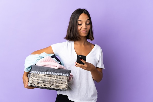 Giovane donna latina che tiene un cestino dei vestiti isolato sul pensiero viola e sull'invio di un messaggio