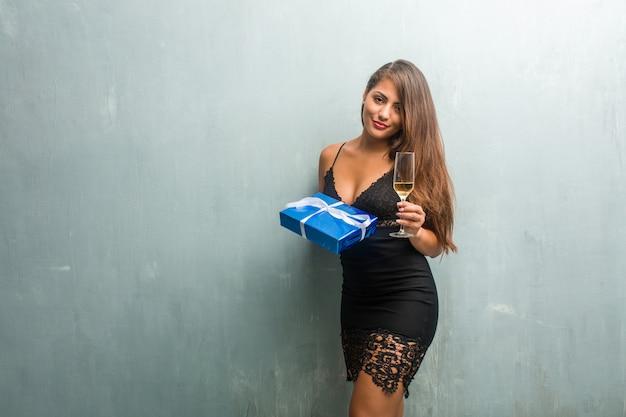 Giovane donna latina che tiene un regalo e una tazza di champagne, si sta divertendo.