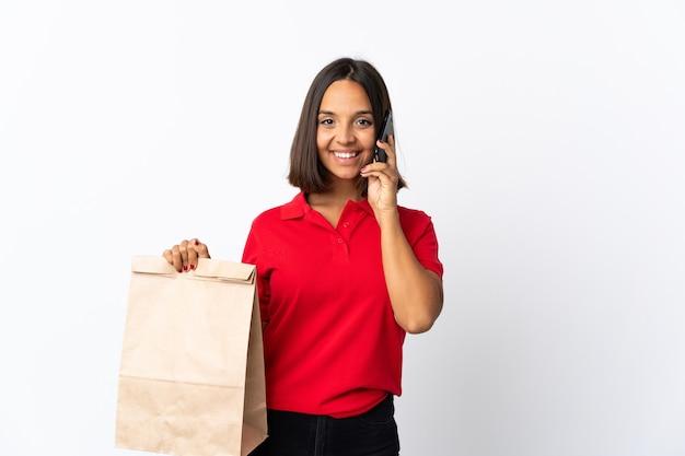 Giovane donna latina che tiene un sacchetto della spesa isolato su bianco mantenendo una conversazione con il telefono cellulare con qualcuno