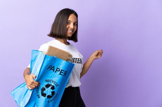 Giovane donna latina che tiene un sacchetto di riciclaggio pieno di carta da riciclare isolato su viola che indica indietro