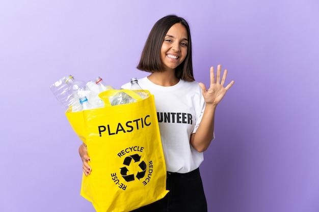 Giovane donna latina che tiene un sacchetto di riciclaggio pieno di carta da riciclare isolato su viola contando cinque con le dita