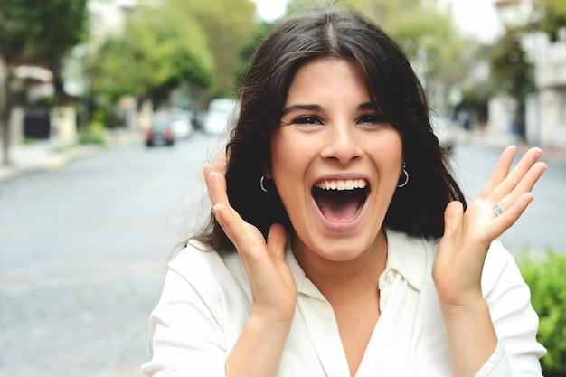 Giovane donna latina con espressione facciale sorpresa.