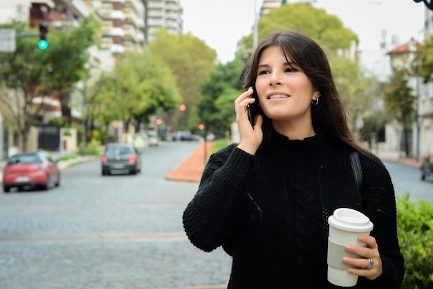 Giovane donna latina con il suo telefono cellulare e tazza di caffè
