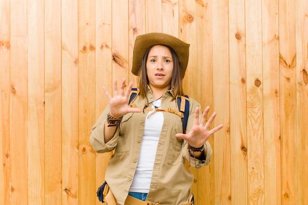 Giovane donna latina dell'esploratore contro il fondo di legno della parete