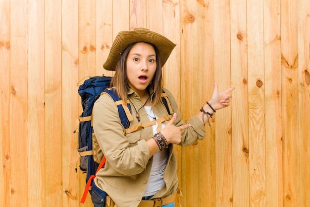 Giovane donna latina dell'esploratore contro la parete di legno