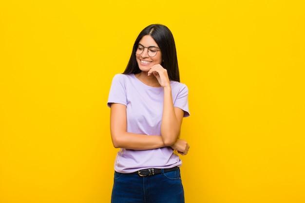 Giovane donna latina graziosa che sorride con un'espressione felice e sicura con la mano sul mento, chiedendosi e guardando al lato sopra la parete