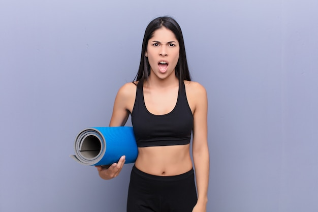 Giovane donna lating con una stuoia di yoga sul muro di cemento