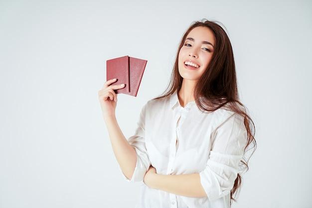 Giovane donna lunga asiatica sorridente felice dei capelli con due passaporti su fondo bianco isolato