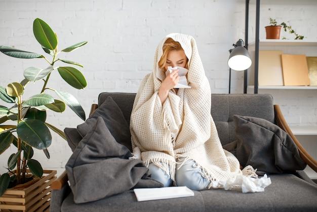 Giovane donna malata con il fazzoletto che si siede sul divano sotto la coperta