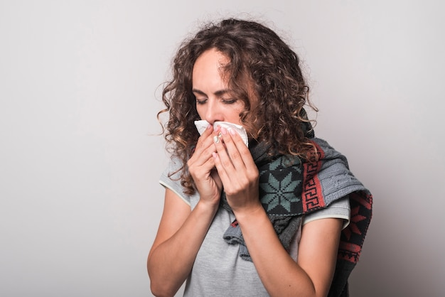 Giovane donna malata con raffreddore e influenza che soffia il naso