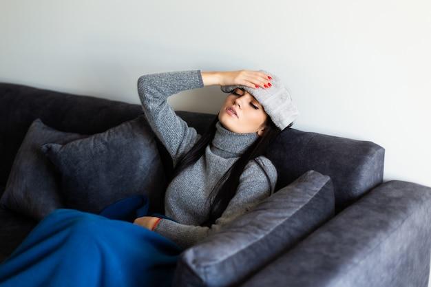 Giovane donna malata in abbigliamento per la casa grigio che si siede sul letto con il funzionamento del computer portatile, esaminante thermometre dopo la misurazione della temperatura. malattia, concetto di libero professionista.