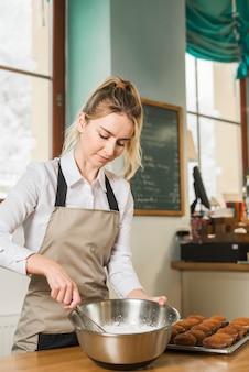Giovane donna mescolando la pastella con frusta nell'utensile preparazione cupcake