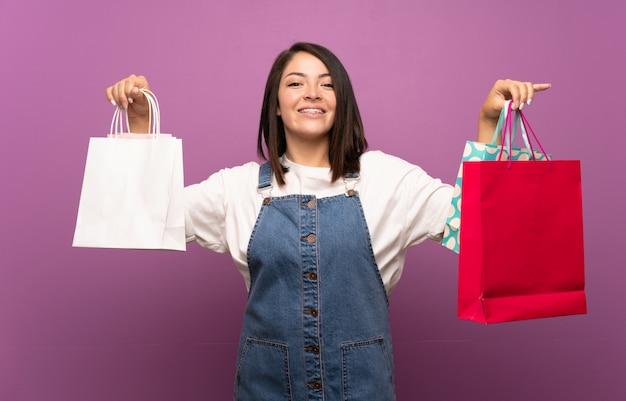 Giovane donna messicana che tiene molti sacchetti della spesa