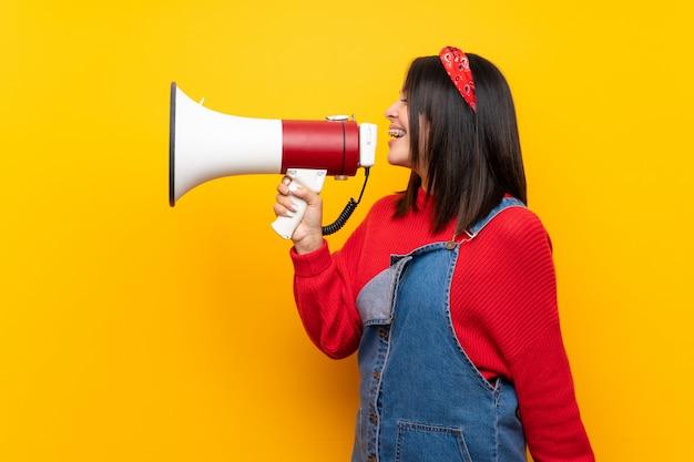 Giovane donna messicana con la tuta sul muro giallo che grida attraverso un megafono