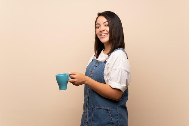 Giovane donna messicana sopra fondo isolato che tiene tazza di caffè calda