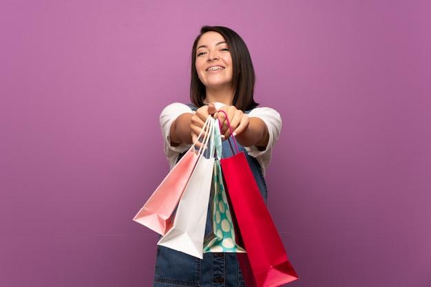 Giovane donna messicana sopra isolata tenendo molti sacchetti della spesa