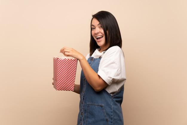 Giovane donna messicana sopra isolato mangiando popcorn