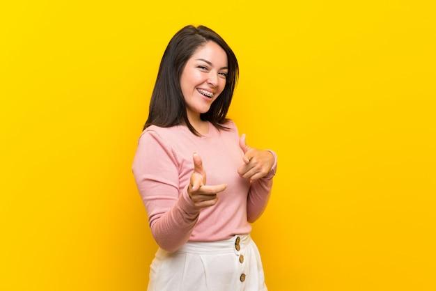 Giovane donna messicana su sfondo giallo isolato che punta verso la parte anteriore e sorridente