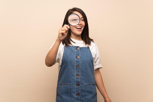 Giovane donna messicana su sfondo isolato tenendo una lente di ingrandimento