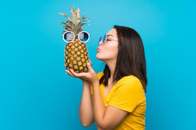 Giovane donna messicana sul blu che tiene un ananas con gli occhiali da sole
