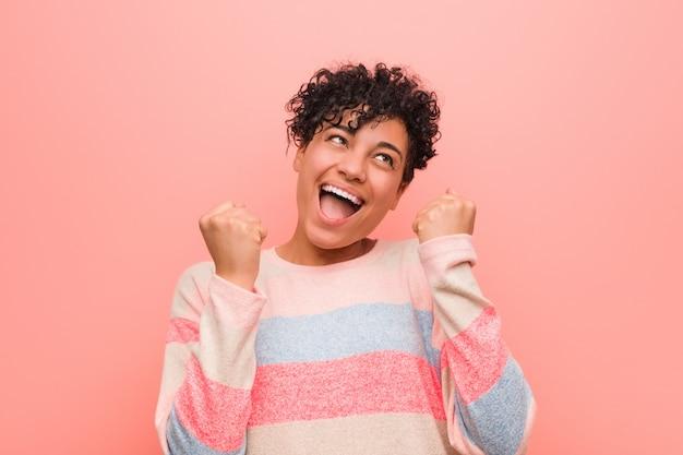 Giovane donna mista afroamericana dell'adolescente che incoraggia spensierata ed eccitata. concetto di vittoria.