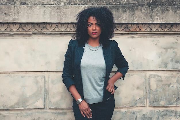 Giovane donna mista con l'acconciatura afro sorridente in background urbano. ragazza nera che indossa abiti casual.
