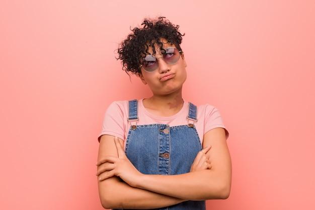 Giovane donna mista dell'adolescente dell'afroamericano stanca di un compito ripetitivo.