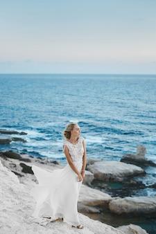 Giovane donna modello con un corpo perfetto in elegante abito bianco lungo in posa sulle rocce sul litorale a cipro