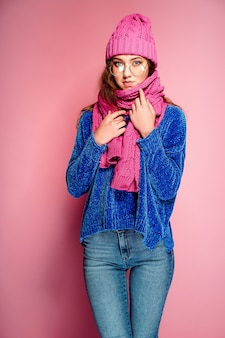 Giovane donna moderna che indossa maglione blu e cappello rosa e sciarpa in posa, rendendo divertente espressione facciale.