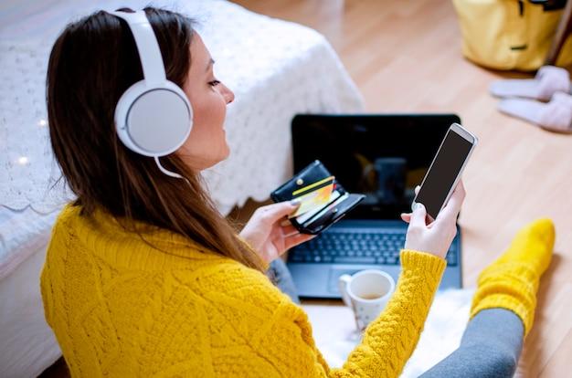 Giovane donna moderna che per mezzo del telefono per fare acquisti su internet con la carta di credito. ordine online dalla casa. negozio online e pagamento