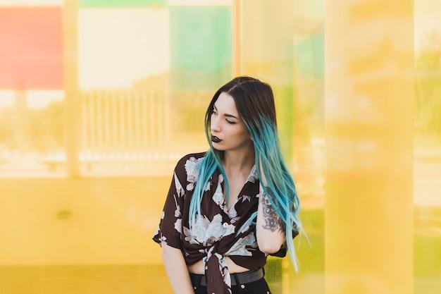 Giovane donna moderna con capelli tinti che stanno davanti a fondo giallo