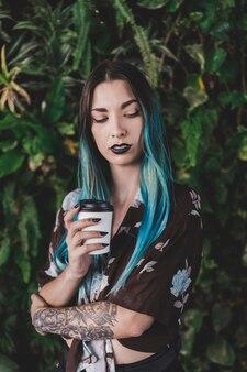 Giovane donna moderna con capelli tinti che tengono la tazza di caffè asportabile