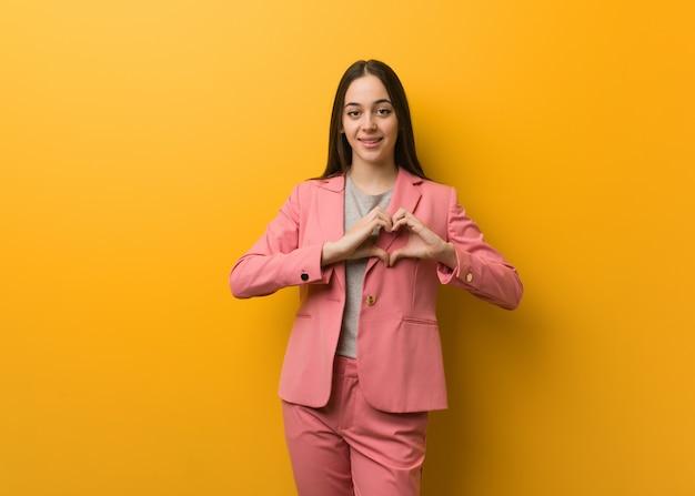 Giovane donna moderna di affari che fa una forma del cuore con le mani