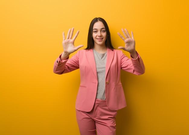 Giovane donna moderna di affari che mostra numero dieci