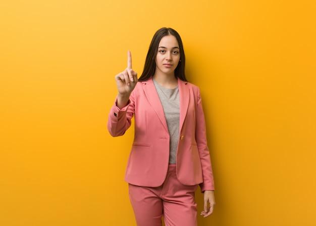 Giovane donna moderna di affari che mostra numero uno