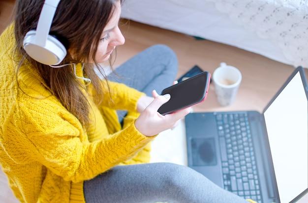 Giovane donna moderna seduta sul pavimento in camera da letto e utilizzando il telefono per lo shopping online con carta di credito