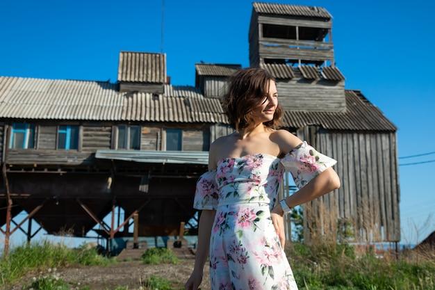 Giovane donna mora abbastanza fresca che cammina all'aperto nel villaggio e che porta il vestito rosa da estate. concetto di vacanze estive al villaggio e stile dal vivo