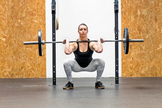 Giovane donna muscolare che fa uno squat anteriore