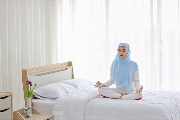 Giovane donna musulmana asiatica che si siede sul letto e che gode della meditazione. la bella donna in indumenti da notte con l'hijab blu pratica l'yoga in camera da letto con pace e calma. concetto di stile di vita sano