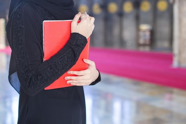 Giovane donna musulmana asiatica del primo piano che tiene corano rosso, in moschea.