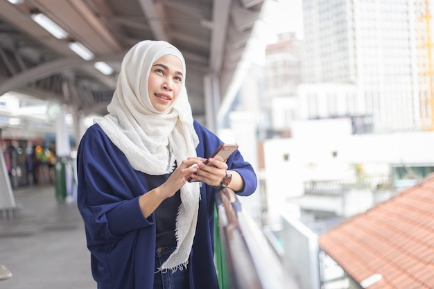 Giovane donna musulmana che per mezzo del telefono sulla stazione dello skytrain.