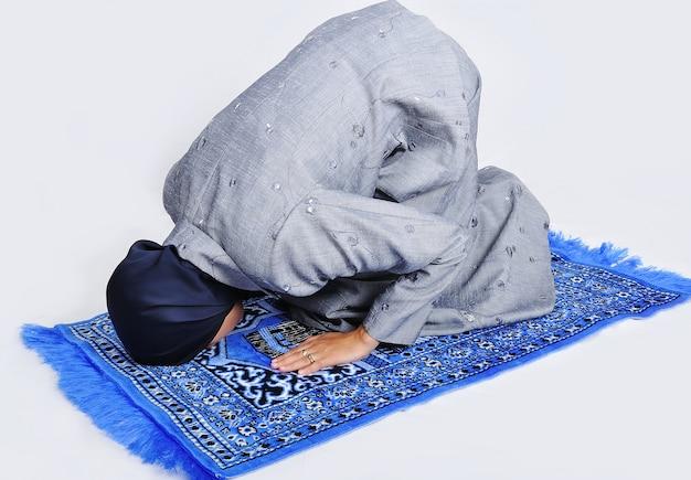 Giovane donna musulmana che prega sul modo tradizionale