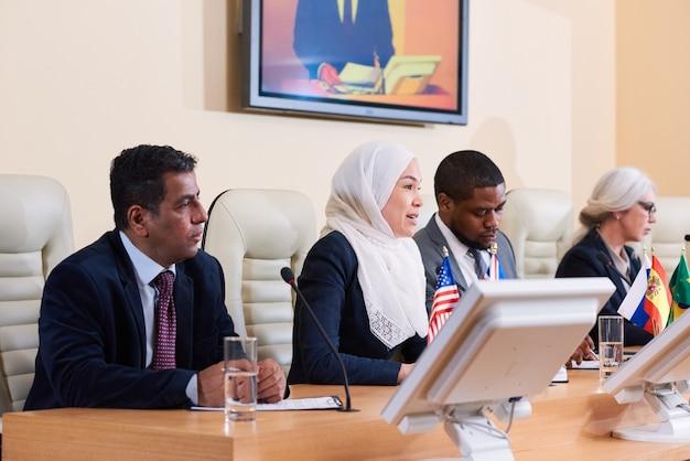 Giovane donna musulmana in hijab bianco che fa discorso a una conferenza politica o d'affari tra colleghi stranieri