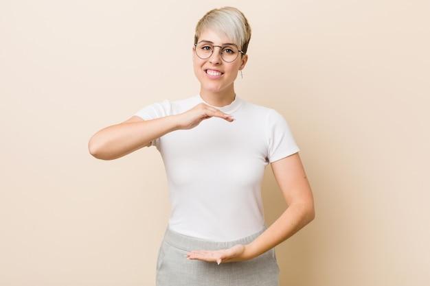 Giovane donna naturale autentica che indossa una camicia bianca che tiene qualcosa con entrambe le mani, presentazione del prodotto.