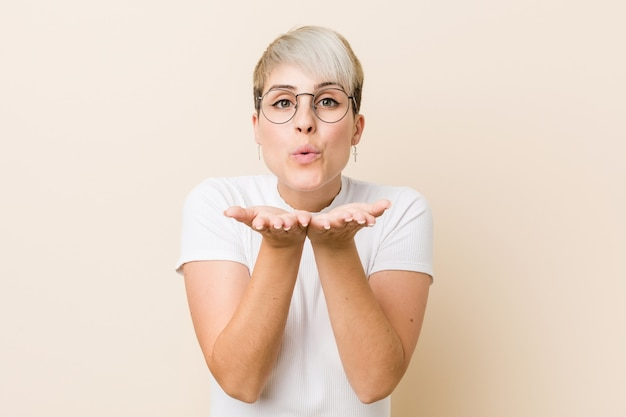 Giovane donna naturale autentica che indossa una camicia bianca piegando le labbra e tenendo le palme per inviare un bacio dell'aria